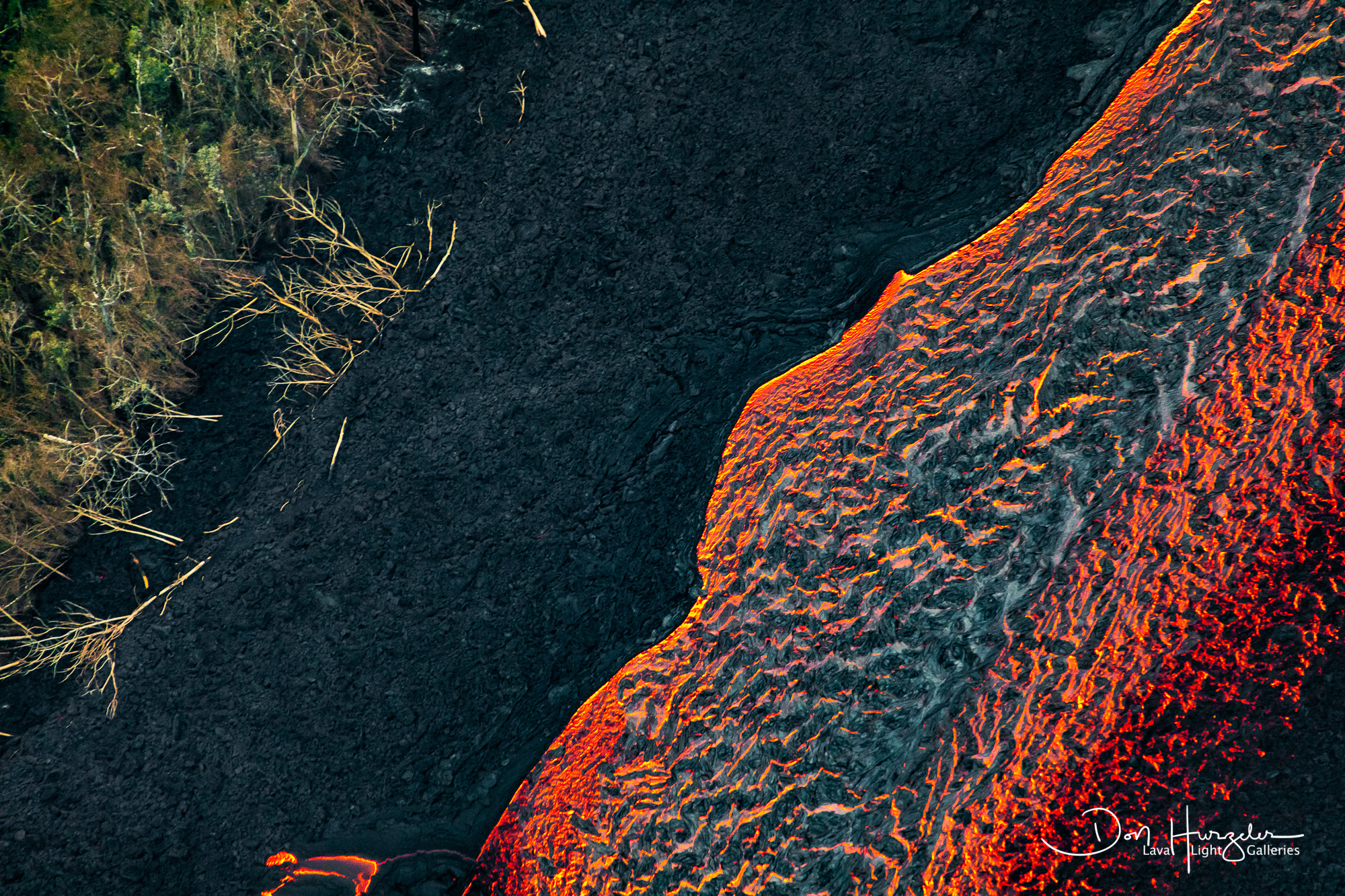 The dark material on top of the red river of lava is lava that is cooling.  It will eventually form a tube that will insulate...