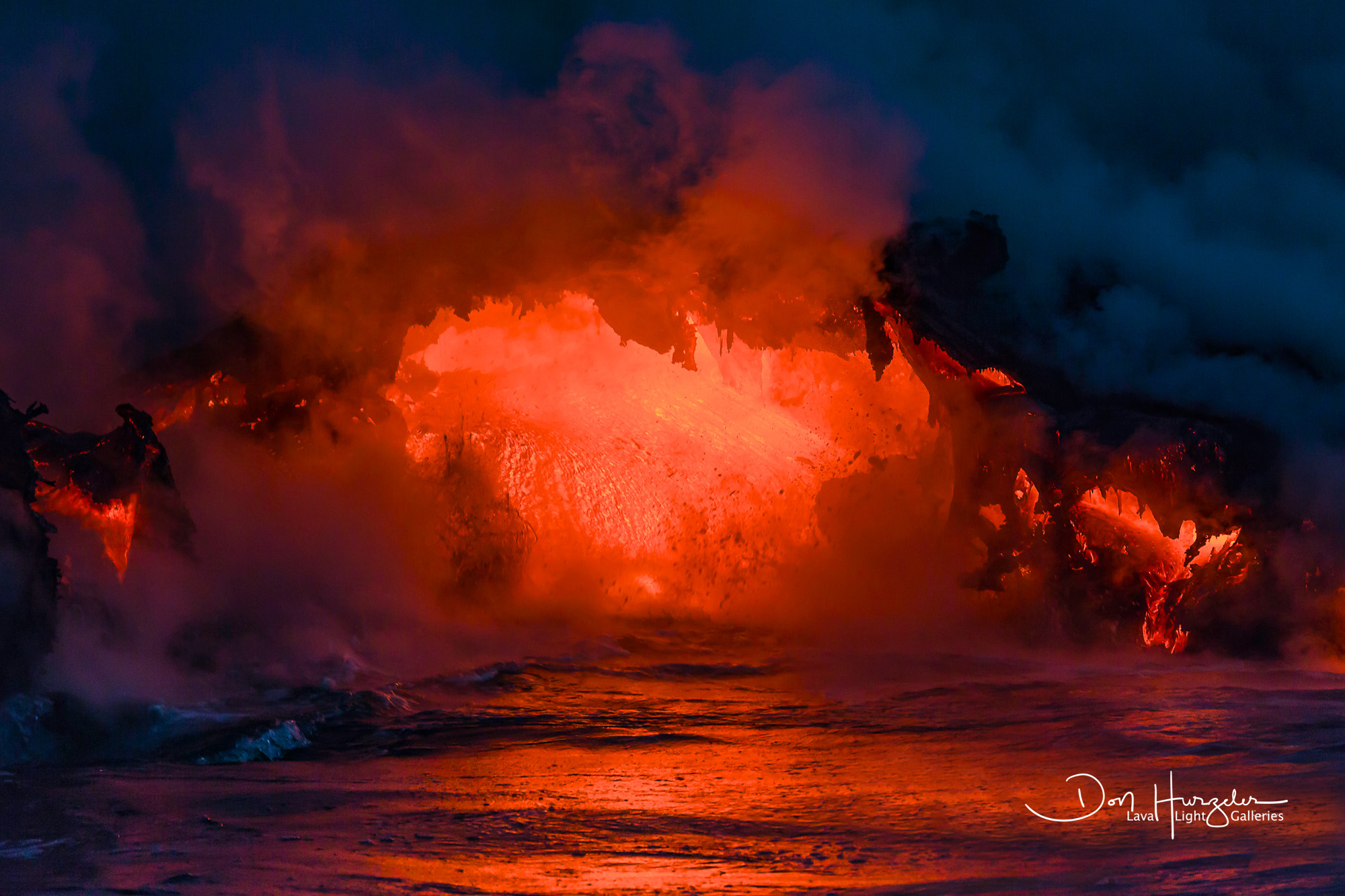 A massive amount of lava pouring from a lava tube directly into the sea.